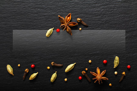 Food presentation background organic various exotic spieces on black slate board with copy space Stock Photo