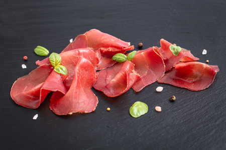 Food appetizer concept Sliced Dried Cured beefs Bresaola on black slate stone board
