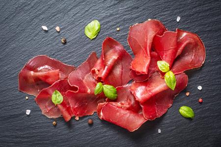 Concepto de aperitivo de alimentos en rodajas de carne seca curada Bresaola sobre placa de piedra pizarra negra Foto de archivo