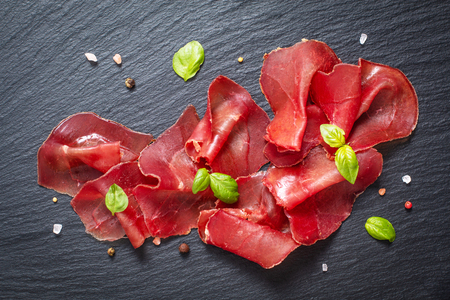 Food appetizer concept Sliced Dried Cured beefs Bresaola on black slate stone board Stock fotó - 110558739