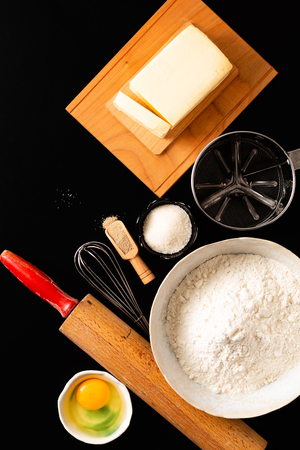 Food preparation concept over head shot kitchen tools for Kneading dough for bakery, pizza or pasta on black background with copy space