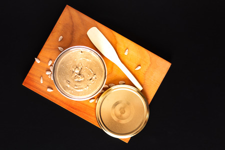 Healthy food concept homemake sunflower butter in glass jar by organic sunflower seeds on black background Stockfoto