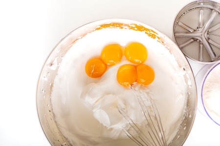 Baking bakery concept whipped eggs mix with ingredients for homemade sponge cake on white background
