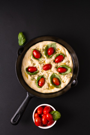 Food concept rising dough for vegan Homemade organic Focaccia in skillet iron pan on black background with copy space Imagens