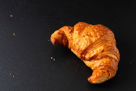 Food concept French croissant on black slate board with copy space