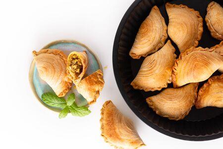 Südostasien Ursprungs-Lebensmittelkonzept hausgemachte Hühnchen-Curry-Puffs auf weißem Hintergrund mit Kopierraum Standard-Bild