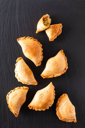 South east Asia origin food concept homemade chicken Curry puffs on black slate stone background with copy space
