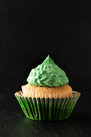 Bakery concept Homemade Sponge vanilla cupcake green tone buttercream on black background with copy space
