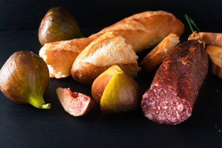Food concept dried cured sausage on black slate board with copy space
