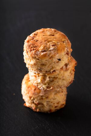Food concept Fresh baked Homemade buttery, salty Ham and cheese scones on black background