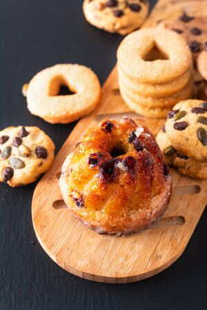 Food Breakfast or snack concept european Gugelhupf, Kougelhopf, kouglof yeast Bundt ring cake with cookies on black background