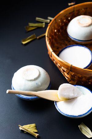 Food dessert concept Thai dessert Kanom Tuay Coconut Rice and pandan Custard in small porcelain cup and bamboo bastket on black background with copy space Stock Photo - 135363676