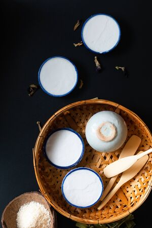 Food dessert concept Thai dessert Kanom Tuay Coconut Rice and pandan Custard in small porcelain cup and bamboo bastket on black background with copy space Stock Photo - 135176690