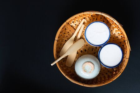 Food dessert concept Thai dessert Kanom Tuay Coconut Rice and pandan Custard in small porcelain cup and bamboo bastket on black background with copy space Stock Photo