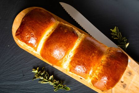 Homemade food concept fresh baked bread braid challah or brioche on black slate stone with copy space