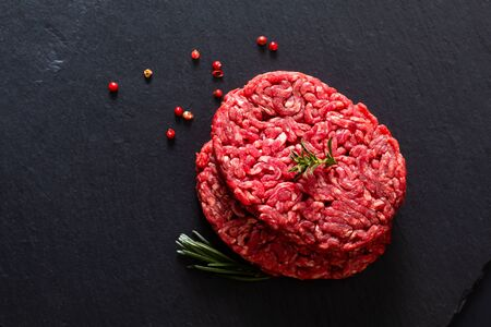 Food concept organic raw minced or ground beef grass feed burger on black slate stone with copy space