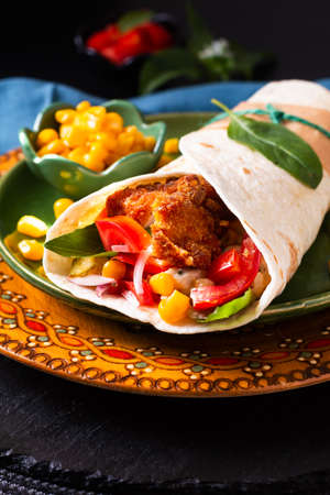 Home cooking concept Organic Homemade Fried chicken burrito tortilla sandwich on color plate and black copy space Standard-Bild
