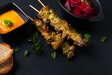Asian food concept  homemade beef satay grilled and spicy peanut spice sauce  on black slate board with copy space Stok Fotoğraf