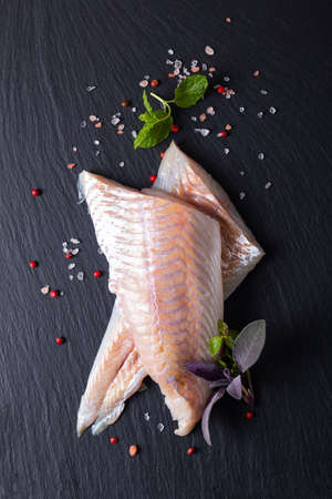 Healthy Food concept top view raw fillets Alaska Pollock, Black Cod on black slate stone board with copy space