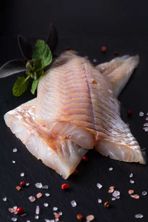 Healthy Food concept raw fillets Alaska Pollock, Black Cod on black slate stone board with copy space