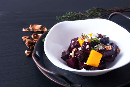 Food concept roasted Beetroot and butternut salad with goat cheese in white ceramic bowl on black background with copy space