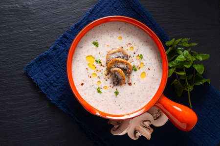 Food concept organic mushroom cream soup in orange ceramic handle bowl on black slate stone with copy space