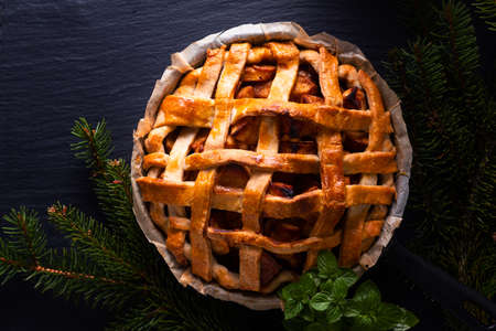 Autumn Winter food concept Homemade rustic organic apple pie in iron skillet pan decorate by pine leaf on black slate stone board with copy space