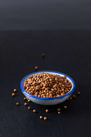 Food ingredient concept organic coriander seed in ceramic bowl on black slate stone board with copy space