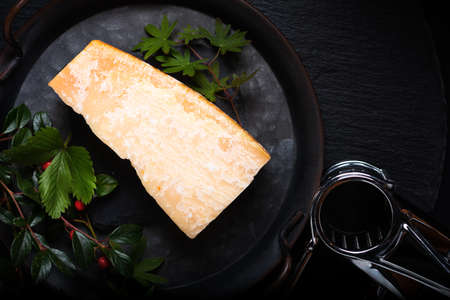 Food Concept organic Parmesan Cheese in rustic iron tray on black slate stone background with copy space