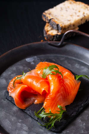 Food concept smoked Trout or Salmom fish slices on black slate stone board with copy space 免版税图像