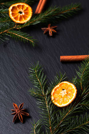 Seasonal background concept Winter or Christmas spices and pine leave on black slate stone board with copy space
