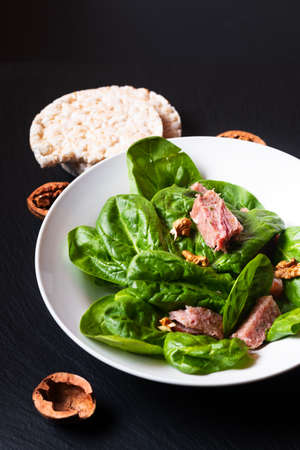 Healthy food concept Spinach salad with French Presskopf in white ceramic dish on black slate stone board with copy space