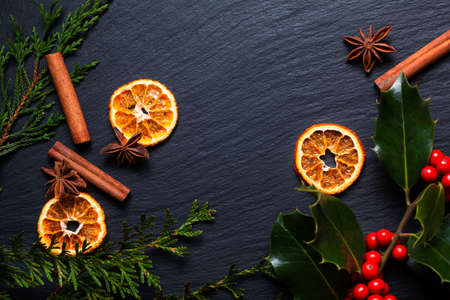 Seasonal background concept Winter or Christmas spices and christmas holly leaf and berry  on black slate stone board with copy space 免版税图像