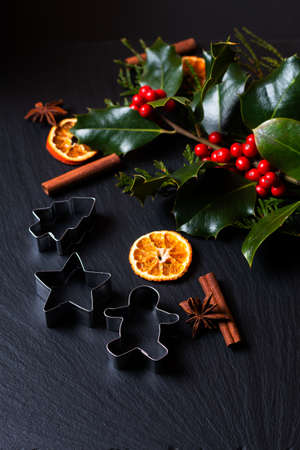 Seasonal background concept Winter or Christmas spices, cookies cutter and christmas holly leaf and berry  on black slate stone board with copy space