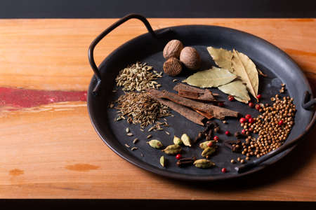 Food concept ingredients of Masala curry spice in vintage iron tray on wood background with copy space
