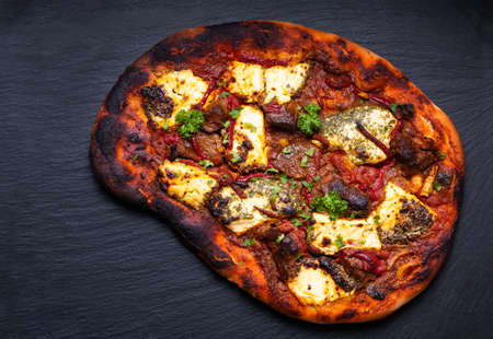 Food concept Homemade rustic beef and goat cheese pizza on black slate stone board with copy space 免版税图像