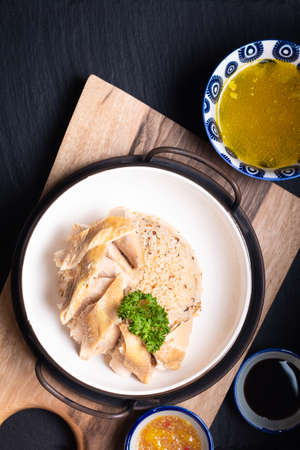 Asian Food concept Hainanese Chicken Rice with sour and sweet soy sauce on wooden board with slate stone background