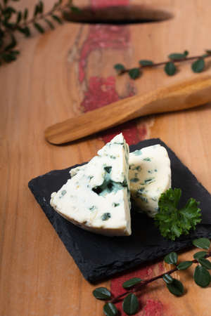 Food concept French Blue cheese Roquefort on black slate plate and wooden board background with copy space