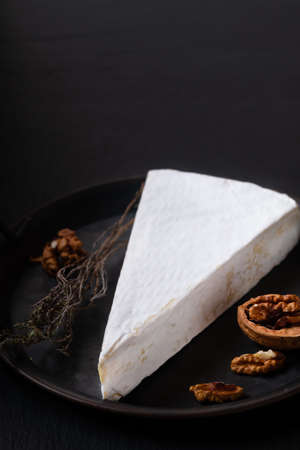 Food concept French Soft Brie cheese in rustic iron plate on black slate stone background with copy space