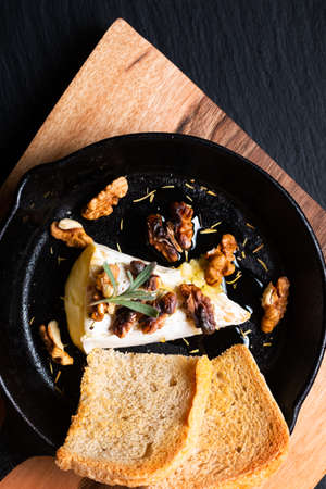 Food concept spot focus homemade Baked Brie cheese with honey and walnuts in skillet iron pan on wooden board with black slate stone copy space