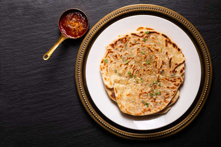 Food concept spot focus homemade Paratha, Parotta or Porotta layered flatbread  on black background with copy space