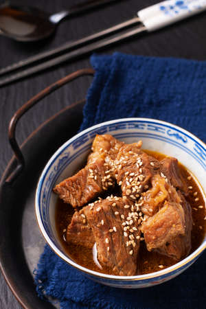 Food concept spot focus Homemade Korean Beef Stew in oriental style porcelain cup on black background with copy space