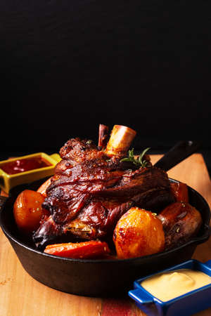 Food concept spot focus homemade rustic Beer Roasted Crispy Pork Knuckle roasted in skillet iron pan with copy space