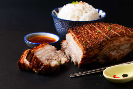 Food Concept spot focus  Homemade Baked Crispy pork belly on black slate stone board with copy space