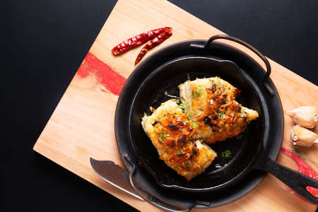 Food concept spot focus homemade butter, garlic, bread crumbs and cheese crunchy Baked cod fish in skillet iron cast pan on black background with copy space Archivio Fotografico