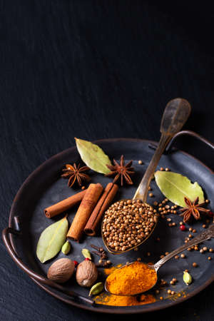 Spot focus Exotic herbal Food concept Mix of the organic Spices coriander seed, clove, cinnamon stick, cardamom pods, bay leaves, star anise in rustic iron tray on black slate stone with copy space