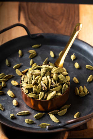 Food Spices concept Cardamom or  cardamon pod in copper cup with copy space