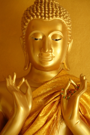 A golden Buddha statue in a teaching gesture on Magha Puja Day photo