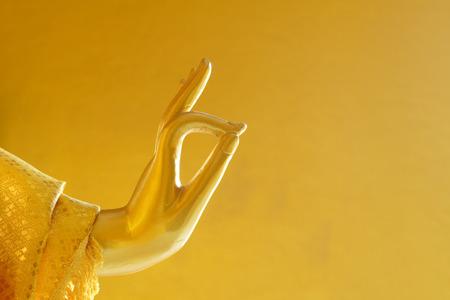 Close up photo of Buddha hand Vitarka Mudra gesture or teaching gesture in a golden atmosphere