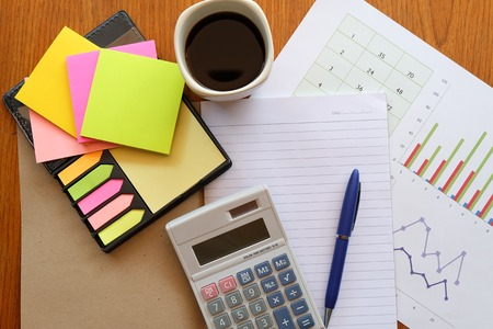 teaching stations: calculator and chart on the wooden table with back coffee Stock Photo